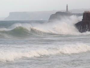 Una ola rompe sobre la isla de Mouro en Santander.