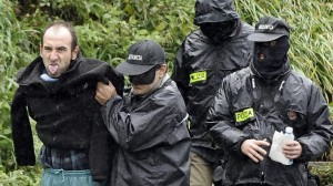 Agentes de la Ertzaintza conducen a Ibon Iparragirre tras registrar un zulo.