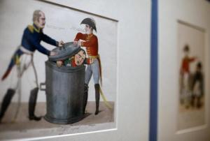"""Un grabado coloreado a mano publicado por Lacroix, en 1815, muestra a Napoleón en una lata de basura con Wellington tapándolo a la fuerza, en la exposició """"Bonaparte y los británicos"""" en el Museo Británico en Londres, el 4 de febrero de 2015. DR"""