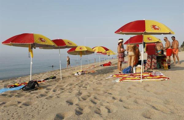 Plantan 12 sombrillas con colores de la bandera de España en la playa de Arenys de Mar