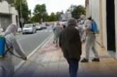 Una decena de personas con trajes de fumigar limpian la calle tras pasar Rivera