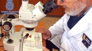 Un policía analiza uno de los pasaportes falsificados. ABC Sevilla.