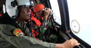 Miembros del equipo de búsqueda y rescate de Indonesia observan desde el aire durante la operación. AFP