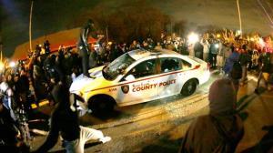 Disturbios en Ferguson. Los manifestantes atacan un coche de policia.